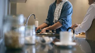 PAN with mid-section of unrecognizable young man washing dishes in kitchen and talking with elderly woman with walking stick