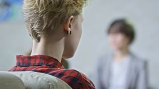 PAN with rack focus of blond teenage girl with short hair putting on earphones and looking away as her frustrated mother gesturing and talking to female psychiatrist in glasses