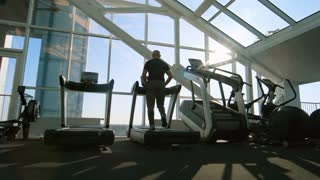 PAN with rear view of senior man with grey hair walking on treadmill during workout in gym with panoramic windows