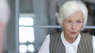 PAN with slow motion of elderly businesswoman in formalwear discussing work with someone on meeting in office