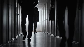 PAN with slow motion of silhouettes of businesswoman and businessmen walking along dark corridor
