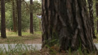 PAN with slowmo of elderly man and woman walking along forest trail and exercising arms