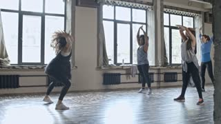 PAN with slowmo of female teacher with curly hair showing warming up exercises to multiethnic group of women before dance class