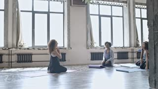 PAN with slowmo of female trainer with curly hair sitting on yoga mat and showing neck stretching exercise to multiethnic group of women