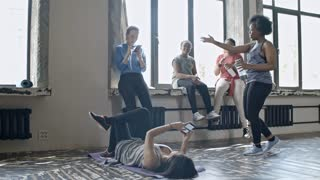 PAN with slowmo of sporty women relaxing on break in dance class: they browsing social media on mobile phones, chatting and practicing moves