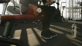 PAN with tilt up of elderly woman sitting on gym bench and putting down dumbbells on floor, then drinking from water bottle after workout