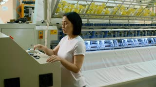Panning shot of female Asian technician working on computer and operating industrial textile machine at factory
