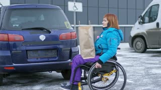 Paraplegic woman on wheelchair bags with groceries in car trunk at parking lot and going to drive