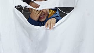 Playful little Syrian refugee boy standing behind torn cloth and looking through hole
