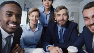 Point of view shot of person having video conference with group of business people, who are smiling and waving hands to camera