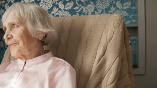 Portrait of smiling retired woman sitting in rocking chair and looking at camera when relaxing at home, tracking shot