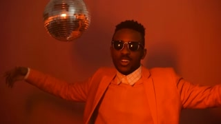 Portrait shot with flashing red light: cool black man in stylish outfit and sunglasses rapping and dancing besides spinning disco ball in studio with pink background