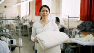 Positive middle-aged Asian woman standing in sewing factory, holding white blanket, looking at camera and smiling