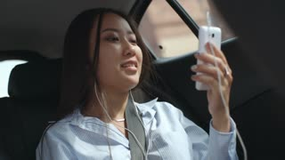 Pretty Asian woman riding in backseat in car, smiling and talking via video call on smartphone with headphones