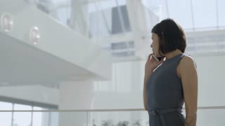 Pretty Latin businesswoman standing in modern office building, smiling, talking on mobile phone and then turning and looking up at sunlight shining through glass roof