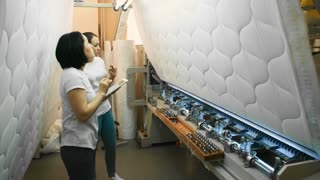 Professional Asian factory worker holding tablet and explaining manufacturing process of quilted fabric to new colleague while working with textile machine at plant