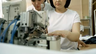 Professional Asian seamstress teaching female colleague how to use sewing machine while working together in textile factory