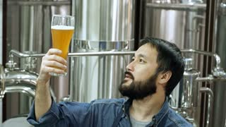 Professional brewery worker of Asian ethnicity examining glass of freshly brewed unfiltered beer, drinking it and looking at camera while checking beverage quality at plant