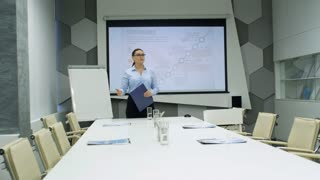 Professional businesswoman standing in front of whiteboard with projected presentation and greeting multiethnic colleagues: men and women entering conference room and sitting at meeting table