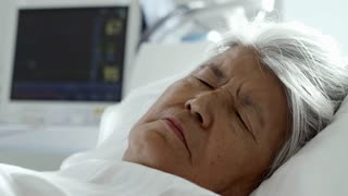 Rack focus of senior female patient with grey hair resting in hospital bed with heart monitor in background
