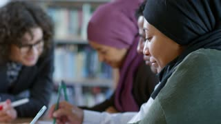 Rack focused shot of attractive female teacher in eyeglasses leaning on table in classroom, smiling and explaining something to women in hijabs and arab man while giving English lesson