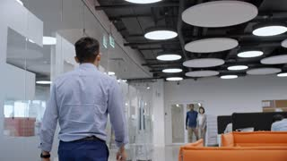 Rear view of businessman going through modern office with stylish hi-tech interior and multi-ethnic employees walking and working at desks