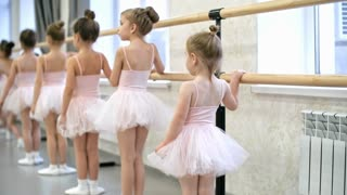 Rear view of group of little girls using ballet barre when doing leg stretching exercises in dance studio