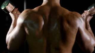 Rear view of muscular shirtless man doing dumbbell curl exercise in dark gym