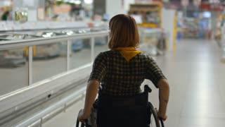 Rear view of young disabled woman riding wheelchair in supermarket, looking at frozen food and turning to aisle