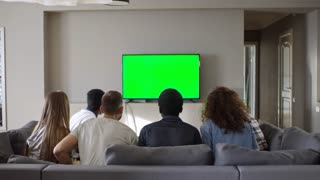 Rear view of young male and female soccer fans sitting on couch and watching sport match on chroma key TV screen. Friends standing up, raising hands and embracing while celebrating victory