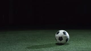 Rear view of young soccer player shooting a ball and running away while training on artificial turf in dark arena
