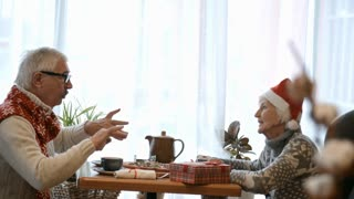Senior couple having Christmas dinner in the cafe: woman in Santa hat sitting at table and listening to elderly man telling a story