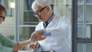 Senior doctor giving medical advice and wrapping hand of middle-aged female patient with elastic bandage in clinic