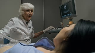 Senior female doctor performing ultrasound exam of abdomen and then telling bad news to Asian female patient