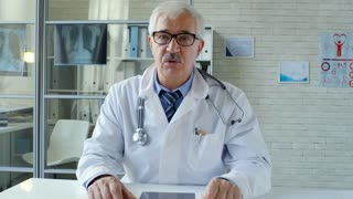 Senior male doctor with stethoscope over his neck sitting at desk in clinic and explaining something at camera