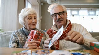 Senior man and woman sitting on couch at restaurant table while having holiday dinner. Elderly couple showing photo of children and telling about family at camera
