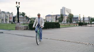 Senior man riding bike towards camera, then getting off and greeting his friend, who uses walking stick