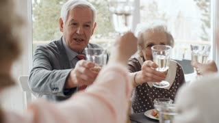 Senior man saying wishes and toasting with wine glasses while having holiday dinner with friends