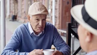 Senior man sitting at table in street cafe, drinking tea and talking to his friend seen from his back