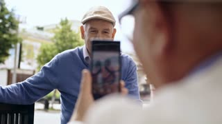 Senior man taking smartphone picture of his friend, who is sitting on bench in pedestrian street
