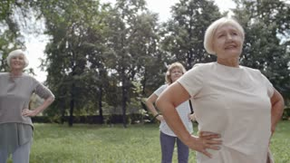 Senior people standing with hands on hips and doing neck warming up exercises during outdoors group workout in park