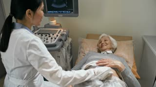 Senior woman standing up from medical couch and putting on sweater after ultrasound examination by Asian female doctor