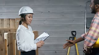 Side view medium shot of friendly Asian woman in hardhat greeting black construction worker with handshake and showing him apartment blueprint attached to clipboard