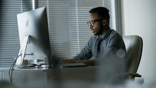 Side view of black man in glasses concentrating on work when typing something using desktop computer at office desk