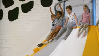 Side view of group of multi ethnic children having fun sliding down into cube pit in indoor amusement park