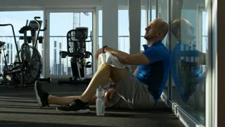 Side view of mature man relaxing after workout at the gym, checking the time on his wristwatch and wiping his face with towel