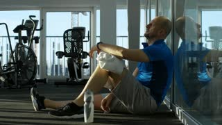 Side view of mature man sitting after workout at the gym, checking the time, drinking water from bottle and wiping his face with towel