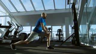 Side view of mature man working out and doing lunges at empty gym