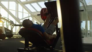Side view of middle-aged man doing leg presses with exercising machine at the gym during sunset
