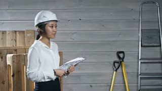 Side view of polite young Asian engineer in safety helmet holding apartment blueprint and showing it to black male construction worker after shaking hands